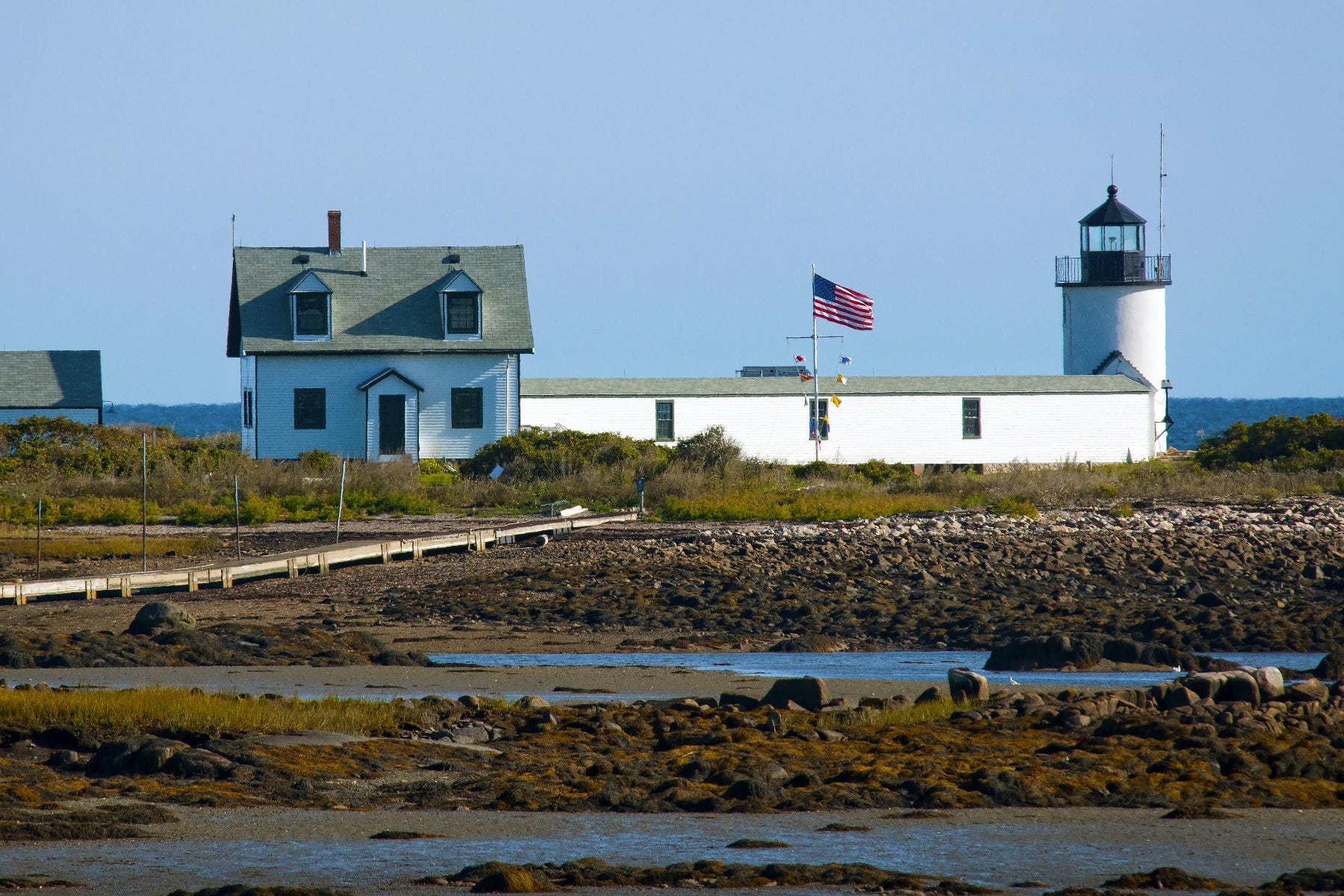 Lighthouse and american flag along the water