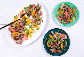 Meat, leafs, and  fruit on plates