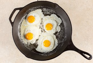 4 eggs being cooked in a cast iron skillet